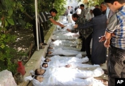 A citizen journalism image provided by the Local Committee of Arbeen shows Syrian citizens trying to identify dead bodies, after an alleged poison gas attack by government forces.