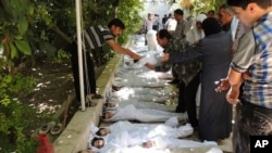 A citizen journalism image provided by the Local Committee of Arbeen which has been authenticated based on contents and AP reporting, shows Syrian citizens trying to identify dead bodies, Aug. 21, 2013, after an alleged poison gas attack by government forces.