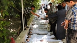 A citizen journalism image provided by the Local Committee of Arbeen which has been authenticated based on contents and AP reporting, shows Syrian citizens trying to identify dead bodies, after an alleged poison gas attack by government forces, Aug. 21, 2013.