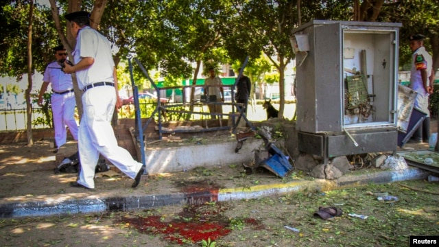 Egyptian security officials inspect a site hit by a bomb attack targeting a traffic security post near a court house in Cairo's Heliopolis district May 2, 2014. One Egyptian soldier was killed and at least seven more people wounded in two suicide attacks