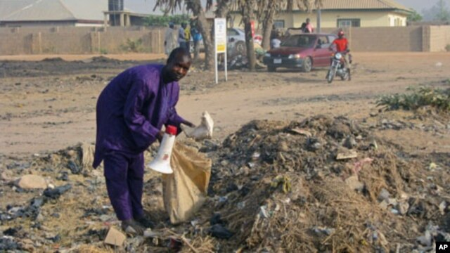 Mallam Muhammadu scavenges a trash dump in the city of Yola, in northeastern Adamawa state, Nigeria, February 14, 2012. He uses the bullhorn to announce his arrival in neighborhoods, where offers to buy unwanted items he can fix and sell.