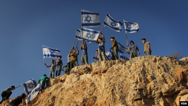Children in the West Bank settlement of Itamar wave Israeli flags on a hilltop. (file) (VOA/Rebecca Collard)