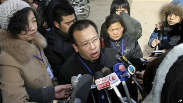 FILE - In this Jan. 22, 2009 file photo, Zhao Lianhai, center, the father of a girl sickened after she drank tainted milk formula, speaks to journalists outside the Intermediate People's Court in Shijiazhuang, in China's Hebei province. Zhao, the Chinese