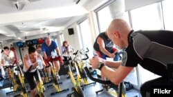 FILE- People are seen exercising in a spinning class. A new study claims short, intense exercise is as good as longer, moderate exercise.
