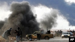 가다피 세력의 공격으로 불타는 반군 진지