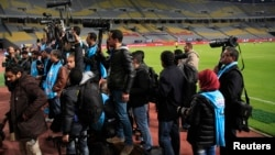FILE - Egyptian photojournalists hold their cameras during a silent protest against preventing them by the officials from covering the Egyptian Premier League derby soccer match, west of Alexandria, Egypt, on February 9, 2016.