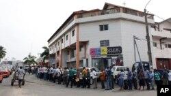 Des fonctionnaires forment une file d'attente devant la branche d'une banque à Abidjan pour percevoir leurs salaires, Côte d'Ivoire, 1er mars 2011.