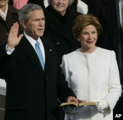 FILE - President Bush takes the oath of office with First Lady Laura Bush at his side, 2005.
