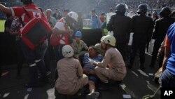 Un hombre herido es asistido después de una mortal estampida en el Estadio Nacional en Tegucigalpa, Honduras, el domingo, 28 de mayo de 2017.