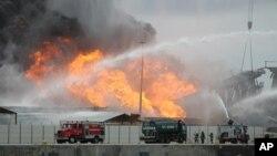 Des pompiers se battent contre l'incendie causé par l'explosion d'un pipeline au port de Leixoes, dans le nord de Portugal, 12 avril 2012.