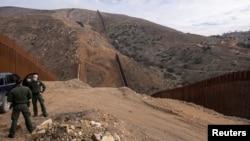 TƯ LIỆU: Nhân viên tuần tra biên giới liên bang đứng gần địa điểm tạm dừng thi công dọc theo bức tường biên giới của Mỹ với Mexico, phía đông San Diego, California, ngày 2 tháng 2, 2021.