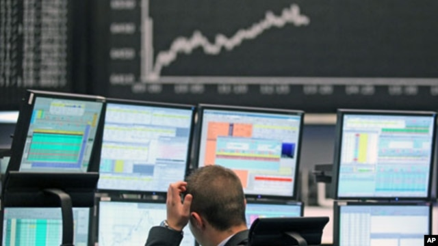 A trader reacts at his desk in front of the DAX board at the Frankfurt stock exchange, May 7, 2012.