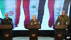 Syria's defense minister Gen. Ali Ayoub, center, holds a news conference with Iran's Chief of Staff of Armed Forces, Maj. Gen. Mohammad Hossein Bagheri, left, and Iraqi army commander, Gen. Osman Ghanemi in Damascus, Monday, March 18, 2019.