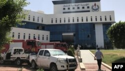 Firefighters and onlookers gather in front of the headquarters of Libya's National Oil Company in the capital Tripoli on September 10, 2018. Armed men stormed the building in Tripoli today where a blast and gunfire were heard, witnesses said.