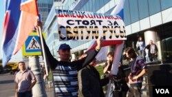 去年秋季在莫斯科爆发了反战和反对俄罗斯干涉乌克兰事务的大游行。一名反对这次游行的人士在游行场外支持手举支持乌克兰东部两个分离地区的旗帜和标语。(美国之音白桦拍摄)