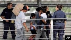 Ever Castillo (kiri) dan keluarganya, imigran dari Honduras, dikawal kembali melintasi perbatasan oleh agen Patroli Bea dan Perbatasan AS, 21 Juni 2018, di Hidalgo, Texas. (Foto: dok).