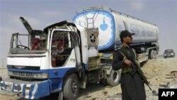 Lính biên phòng Pakistan đứng gác cạnh một xe tải chở tiếp liệu cho các lực lượng NATO ở Afghanistan, ngày 30/9/2010