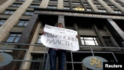 "FILE - A lone activist protests against a restrictive law targeting foreign-funded NGOs working in Russia, outside a government building in Moscow, July 6, 2012. His placard reads ""Tightening the law concerning NGOs [attests to] the paranoia of the authorities."""