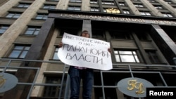FILE - An activist protests against a restrictive law targeting foreign-funded NGOs working in Russia, outside the Duma, Russia's lower house of parliament, in Moscow.