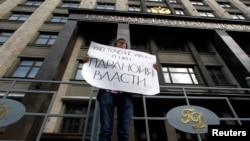 "FILE - A lone activist protests against a law targeting foreign-funded NGOs in Russia, outside the Duma, Russia's lower house of parliament, in Moscow. His placard reads ""Tightening laws concerning NGOs [attests to the] the paranoia of authorities."""