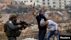 14일 요르단 서안과 가까운 유대인 정착촌 주변에서 이스라엘 군인과 사복 경찰관이 팔레스타인 시위 참가자를 체포하고 있다.