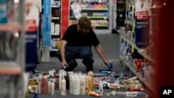 Seorang pria memunguti barang-barang yang berjatuhan akibat gempa di sebuah toko di di La Mirada, California (28/3). (AP/Jae C. Hong)