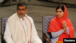 Kailash Satyarthi (kiri) dan Malala Yousafzai pada upacara di Oslo, Norwegia hari Rabu (10/12).
