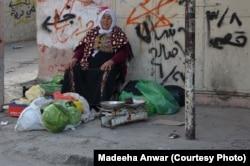 دھیشہ کیمپ میں ایک معمر فلسطینی خاتون سبزیاں بیچتے ہوئے