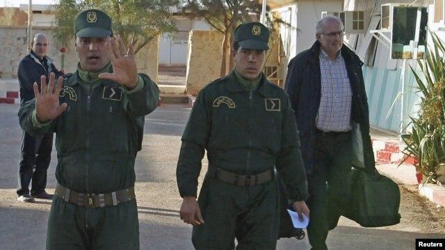 Tentara Aljazair mengawal seorang sandera Norwegia (kanan) yang berhasilnya meraka bebaskan dari penyanderaan oleh para militan (19/1).