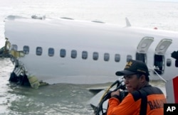 FILE - A rescue worker prepare to retrieve a Lion Air jet plane's cockpit voice recorder out of the wreckage of the plane near the Ngurah Rai International airport in Kuta, Bali, Indonesia on Monday, April 15, 2013. (AP Photo/Firdia Lisnawati)