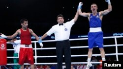 Pakistan's Muhammad Waseem (L) and Australia's Andrew Moloney react to the result of their boxing match at the 2014 Commonwealth Games in Glasgow, Scotland August 2, 2014. (REUTERS/Russell Cheyne)