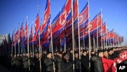 朝鲜人手举国旗在平壤金日成广场游行向朝鲜劳动党表忠诚.(2016年2月25日)