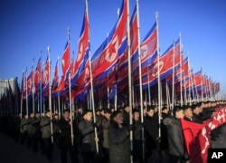 FILE - North Koreans parade with the North Korean flag in Kim Il Sung Square in Pyongyang to show their loyalty to the Workers' Party, Feb. 25, 2016.