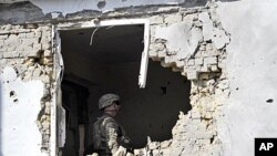 A US soldier checks the damage at offices of the U.N.'s refugee agency, the UNHCR, caused by a suicide bomber, in Kandahar, Afghanistan. A suicide vehicle bomb struck a checkpoint in a neighborhood housing United Nations and international aid groups' offi