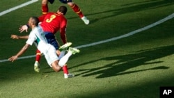 Nigeria's Sunday Mba, left, is airborne after colliding with Spain's Gerard Pique.