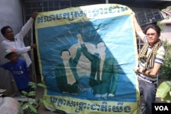 Cambodia National Rescue Party activists, Khan Lai, left, and Chham Sophan, right, held up a CNRP poster in Poipet, Banteay Meanchey province. (Sun Narin/VOA Khmer)
