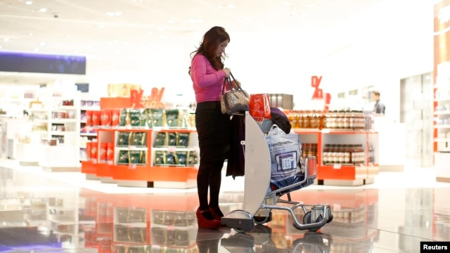 FILE - A woman from China at a duty-free store that offers new Mandarin-speaking personal shopper service at the airport in Frankfurt, Germany, Nov. 14, 2012.