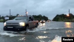 Cars drive through a flooded road in Mobile, Alabama, U.S., October 8, 2017, in this still image taken from a video obtained from social media. Michael Schubert/social media/via Reuters.