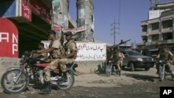Pakistani paramilitary troops patrol on a street to ensure security in Karachi, Pakistan on Sunday, Oct. 16, 2010. Gunmen have killed at least 21 people in Karachi in the past 24 hours, raising tensions in Pakistan's largest city as voters headed to the p