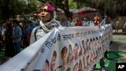 FILE - A Tibetan exile sings the national anthem as he holds a banner with others showing the portraits of Tibetan self-immolators during a protest in New Delhi, April 25, 2014.