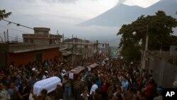 La gente lleva los ataúdes de siete personas que murieron durante la erupción del Volcán de Fuego, hacia el cementerio en San Juan Alotenango, Guatemala, el lunes, 4 de junio de 2018.