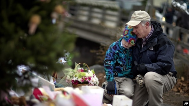 December 16: David Freedman, right, kneels with his son Zachary, 9, as they visit a sidewalk memorial for the 26 people, including 20 children, who were killed at Sandy Hook Elementary School in Newtown, Connecticut.
