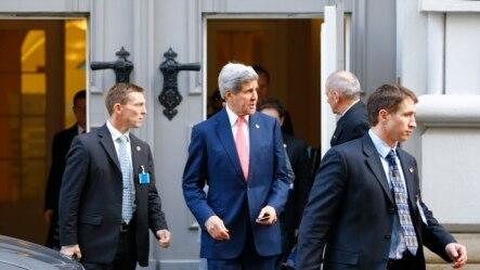 2014年11月23日,美国国务卿克里(中)在安全人员的保护下离开维也纳谈判地点。