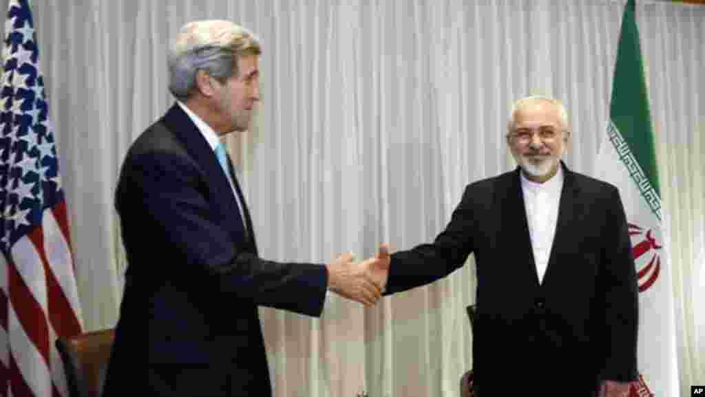 امریکی وزیر خارجہ جان کیری ایران کے وزیر خارجہ جواد ظریف سے ہاتھ ملا رہے ہیں۔