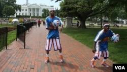 Cheese Chisholm y TooTall Hall, de los Harlem Globetrotters, jugaron y encantaron frente a la Casa Blanca el miércoles 29 de mayo. [Foto: Mitzi Macias, VOA].