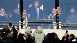 Trump saluda a los espectadores durante el descanso en el juego de fútbol americano entre el Ejército y la Armada, en Baltimore.
