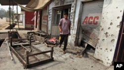 An Indian villager walks near damaged shops hit by mortar attack allegedly fired from the Pakistan's side in Arnia Sector near the India-Pakistan international border, about 47 kilometers (30 miles) from Jammu, India, Oct. 7. 2014.