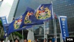 多名香港自治運動成員在遊行終點特區政府總部外,高舉支持本土農業的標點及港英時代的龍獅旗 (美國之音湯惠芸拍攝)