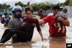 Una mujer embarazada es sacada de un área inundada por las lluvias del huracán Eta en Planeta, Honduras, el jueves 5 de noviembre de 2020.