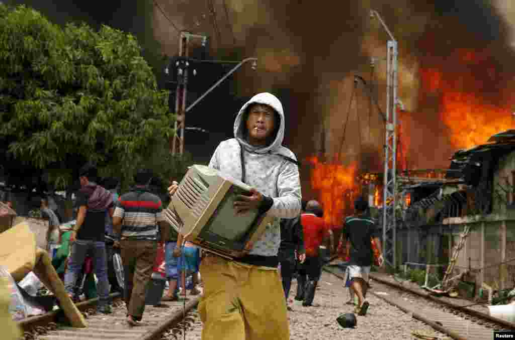 A man carries a television while a fire ranges over a slum area next to railway tracks in Kampung Bandan, North Jakarta, Indonesia.